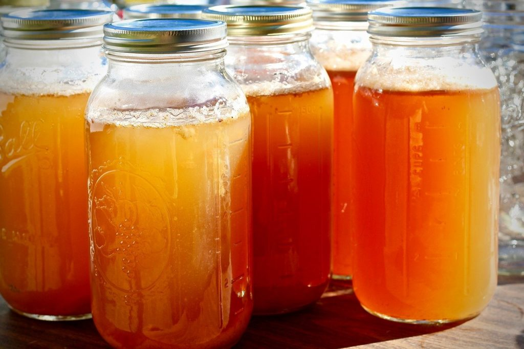 5 bottles with brass coloured lids, full of apple cider vinegar. Golden and cloudy almost looking like honey.